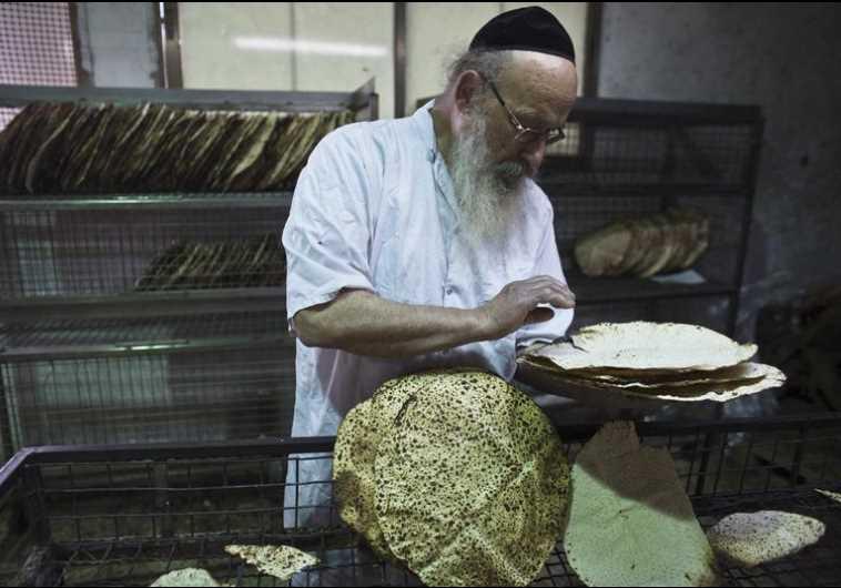 An ultra-Orthodox Jewish man inspects freshly baked matza