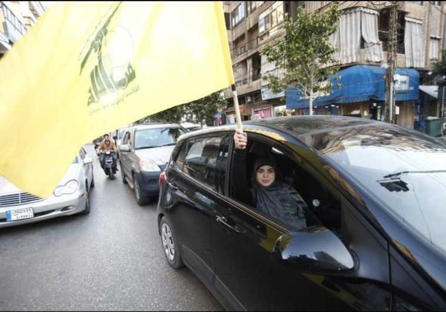 A Hezbollah supporter waves a flag in Beirut's southern suburbs