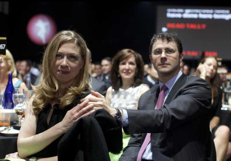 Chelsea Clinton and her husband Marc Mezvinsky (R) sit in the audience at the Robin Hood Foundation