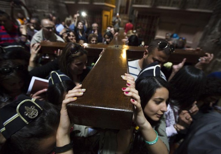 Christians carry a cross after a procession in the Church of the Holy Sepulchre on Good Friday