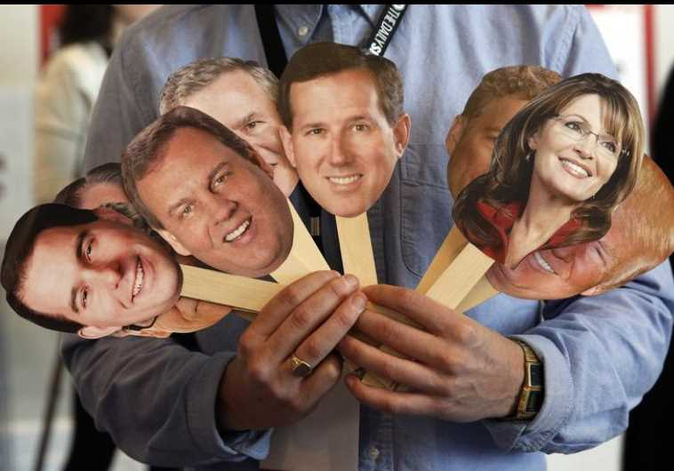 A member of the media conducts an interview while holding images of potential GOP candidates