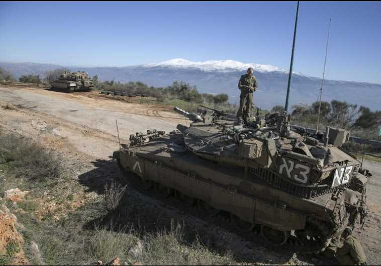 An IDF soldier stands atop a tank near the Lebanese border