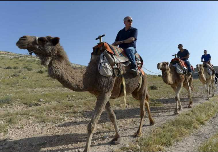 Prime Minister Benjamin Netanyahu (L) and his sons ride camels as they vacation in Israel