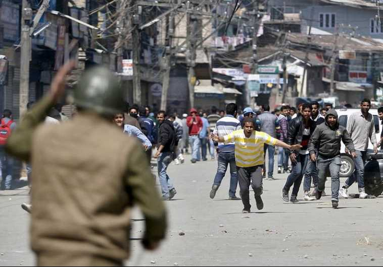 Kashmiri protesters run towards Indian security personnel during a demonstration
