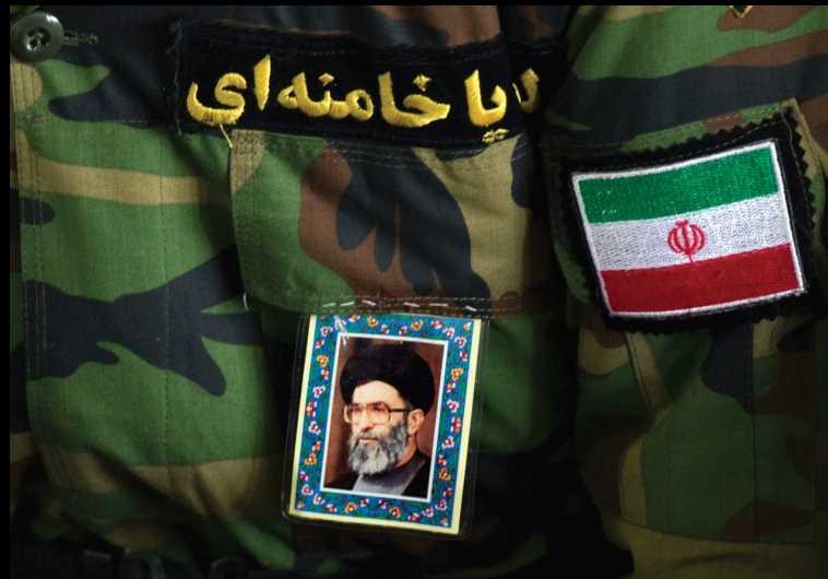 A WORSHIPPER pastes a portrait of Iran's Supreme Leader Ayatollah Ali Khamenei