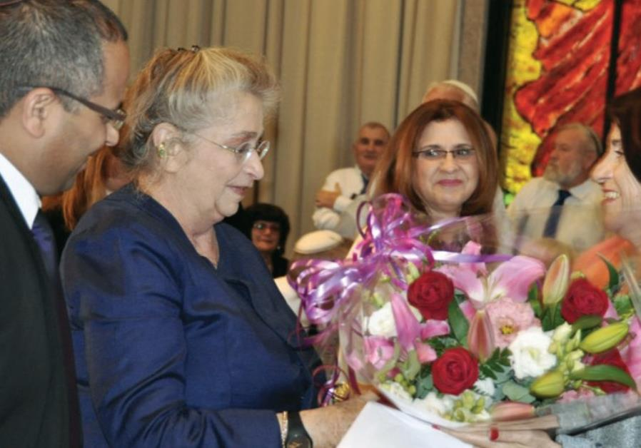 Nechama Rivlin (center) accepts a bouquet from author Dina Kit