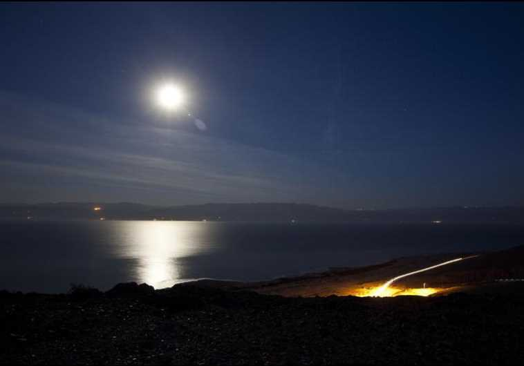 The moon shines in the night sky above the Dead Sea