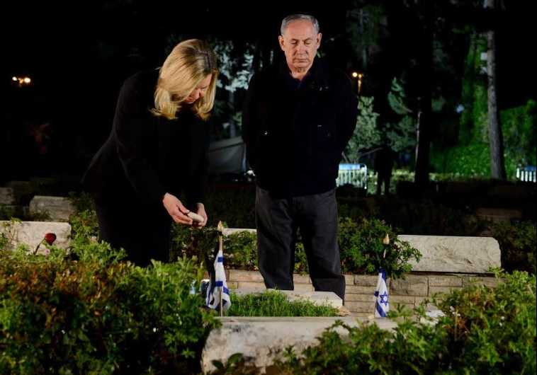 Prime Minister Benjamin Netanyahu (R) and his wife, Sara, pay respects to the premier's late brother