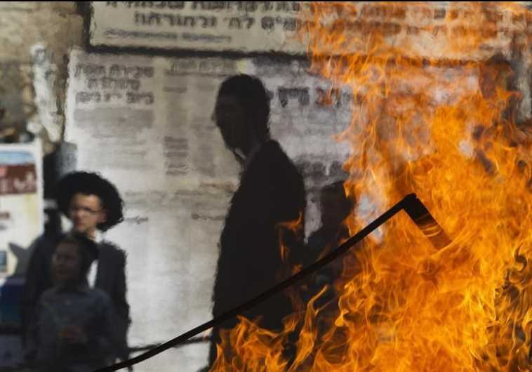 Ultra-Orthodox Jewish bystanders are seen through a heat mirage from a fire set by demonstrators