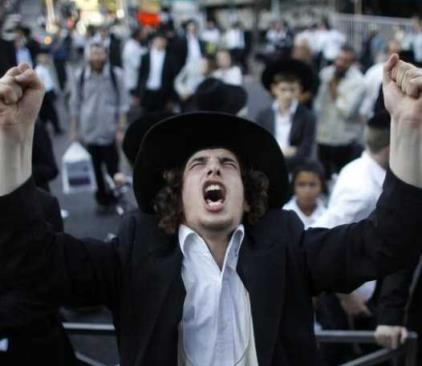 An ultra-Orthodox Jew gestures during a protest in the Mea Shearim neighborhood of Jerusalem