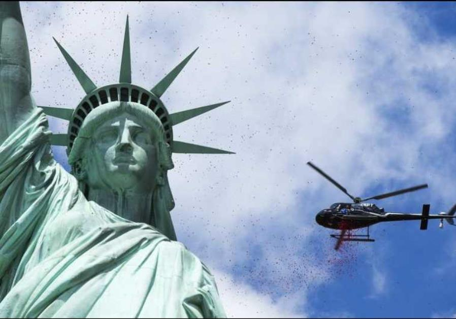 A helicopter flies above the Statue of Liberty in New York Harbor