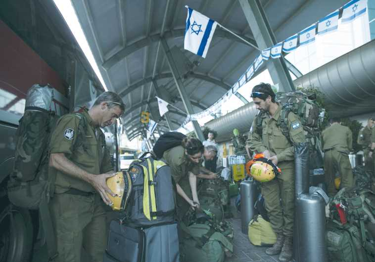 Members of an IDF aid delegation prepare their equipment as they wait for a flight to Nepal