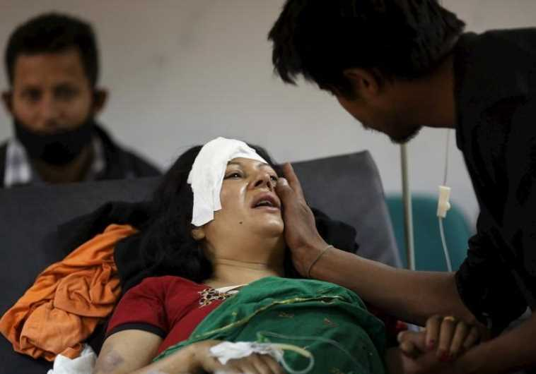 A boy comforts his mother who was injured during an earthquake, at a trauma center in Kathmandu