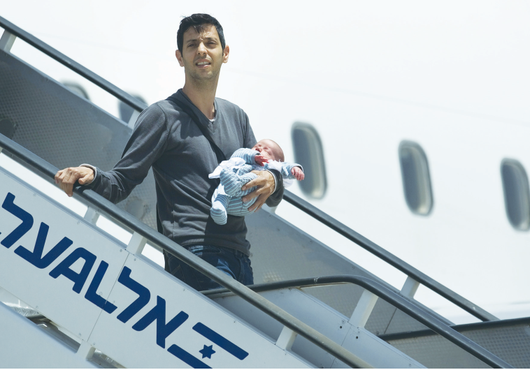 AN ISRAELI holds his surrogate-born baby as he disembarks yesterday from a plane at Ben-Gurion Airpo