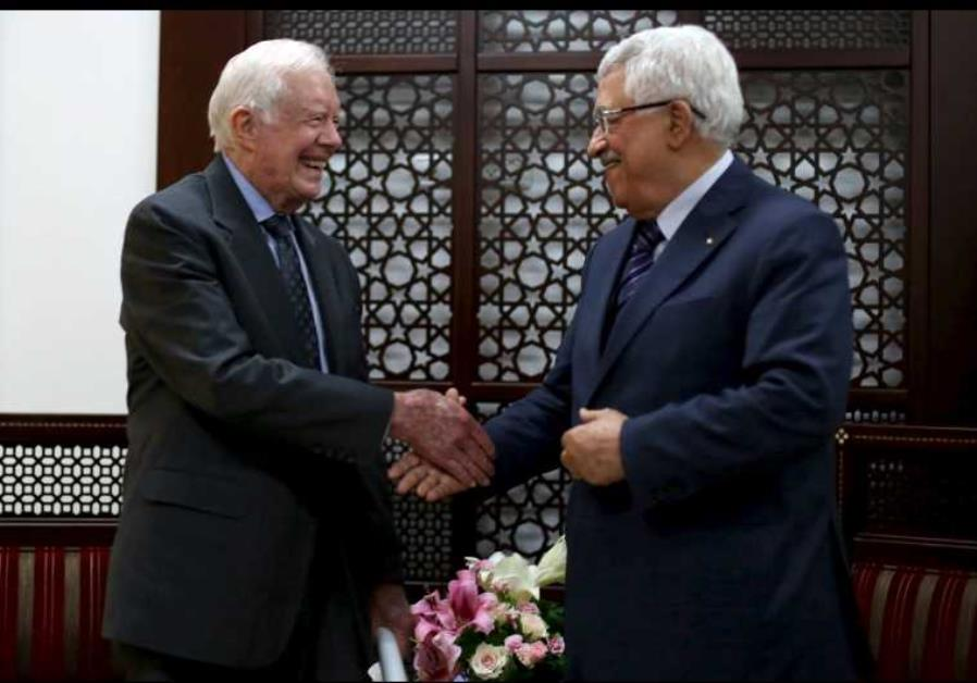 Palestinian President Mahmoud Abbas (R) shakes hands with former US president Jimmy Carter