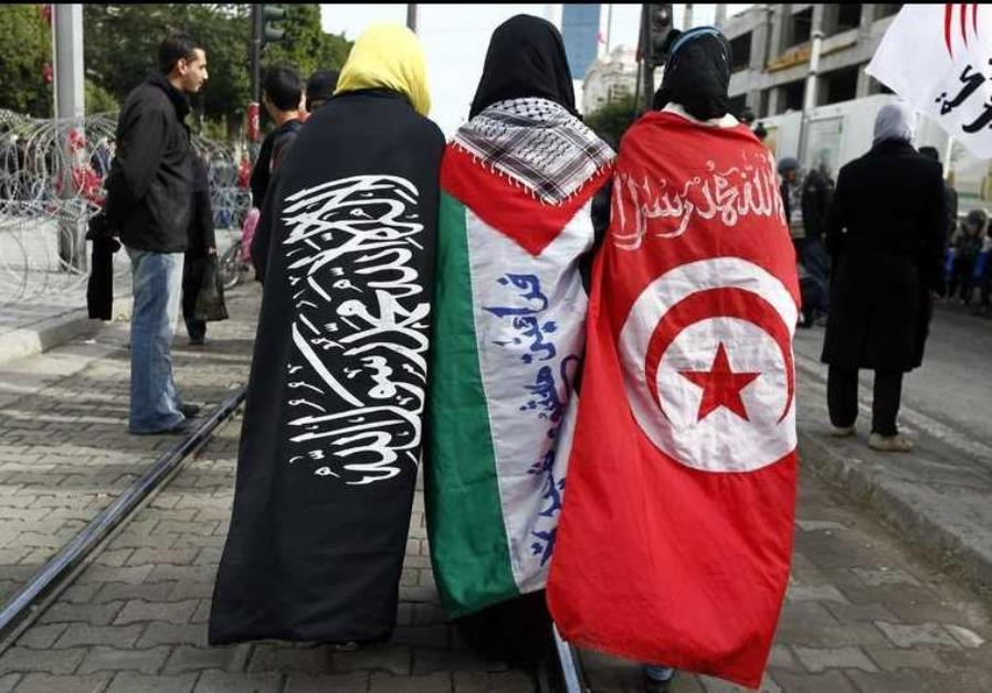Girls walk the street dressed in (L-R) the Salafi, Palestinian and Tunisian flags