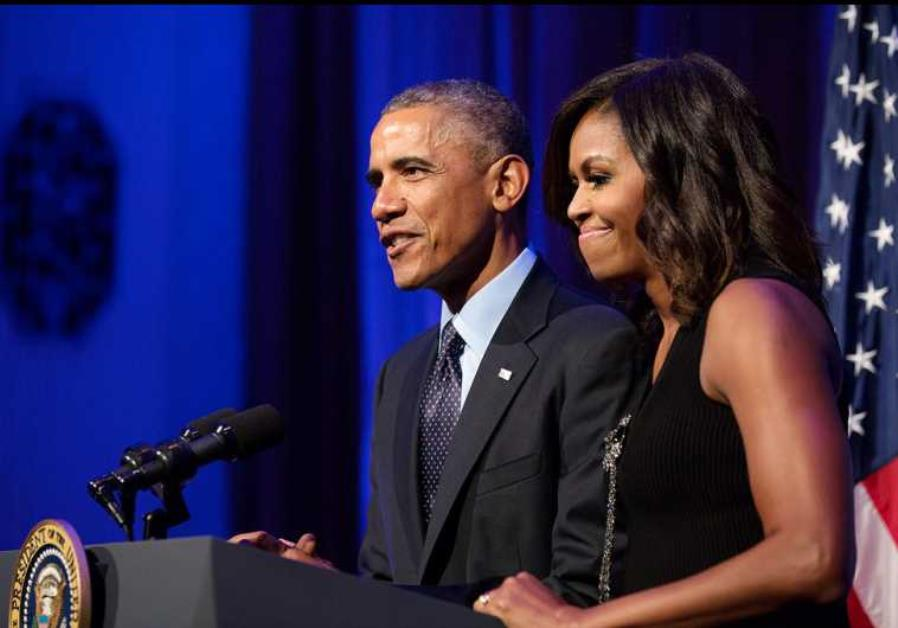 President Barack Obama (L), with First Lady Michelle Obama, delivers remarks during a reception