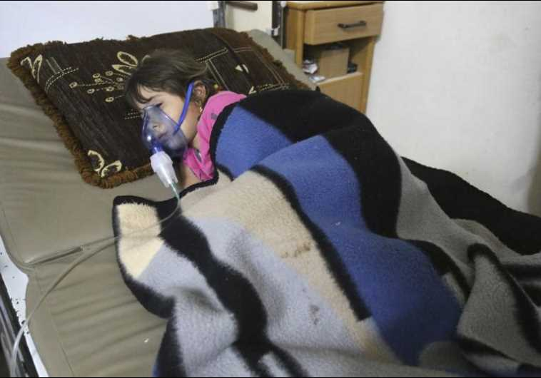A girl, affected by what activists say was a gas attack, receives treatment inside a hospital