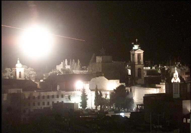 A flare and bullets fly over Bethlehem's center during an IDF attack on the Church of the Nativity