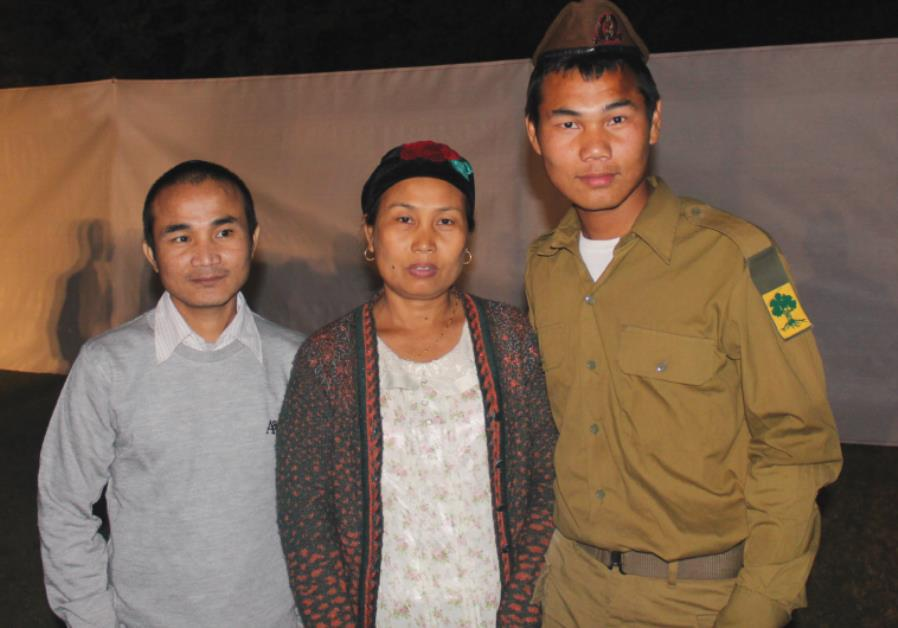 SHLOMO TOUTHANG embraces his parents, Daniel and Hoikhoneng, after the ceremony on Tuesday in Tel Av