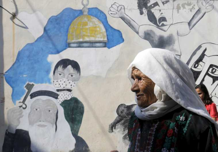 A Palestinian woman walks at Al-Baqaa Palestinian refugee camp near Amman
