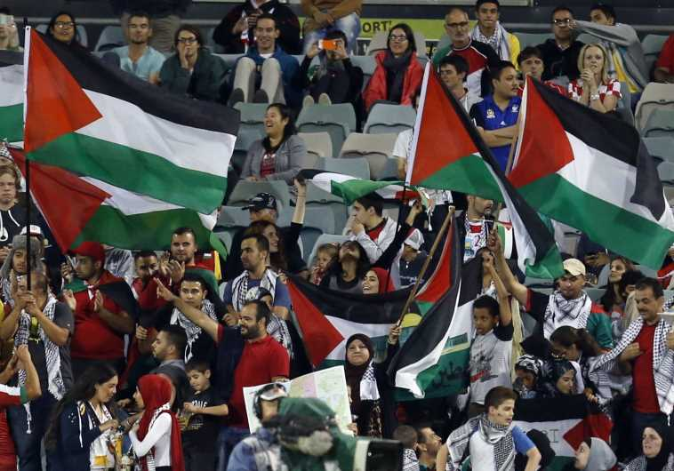 Fans of the Palestinian national team wave flags during their Asian Cup Group D soccer match against
