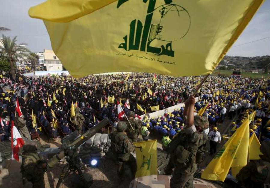 A Hezbollah member carries a Hezbollah flag while leader Hassan Nasrallah talks on a screen