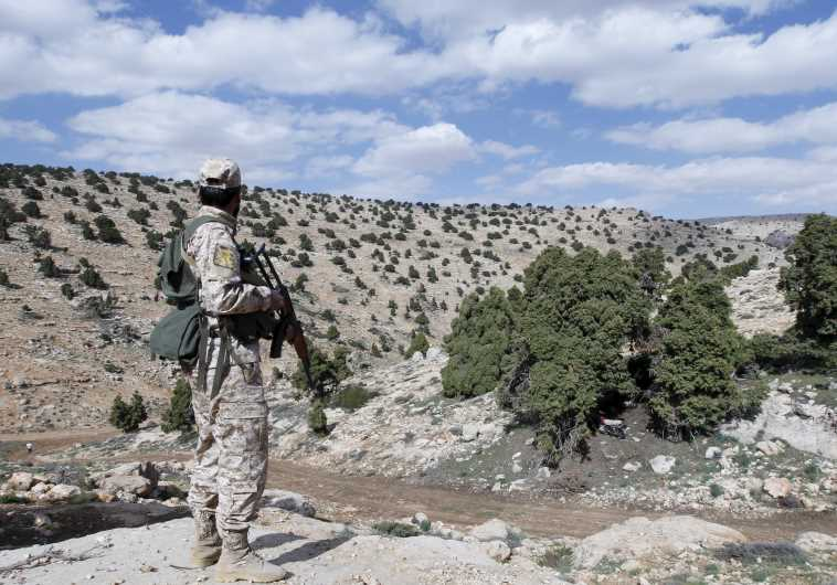 A Lebanon Hezbollah fighter carries his weapon as he stands in Khashaat, in the Qalamoun region