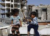 Palestinian children play with a toy gun in front of homes ruined during Operation Protective Edge