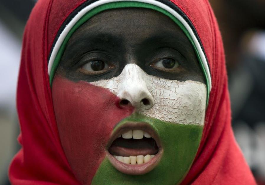 A protester with her face painted in the colors of the Palestinian flag chants in London