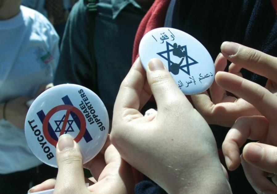 WOMEN HOLD pins that advocate a boycott against Israel