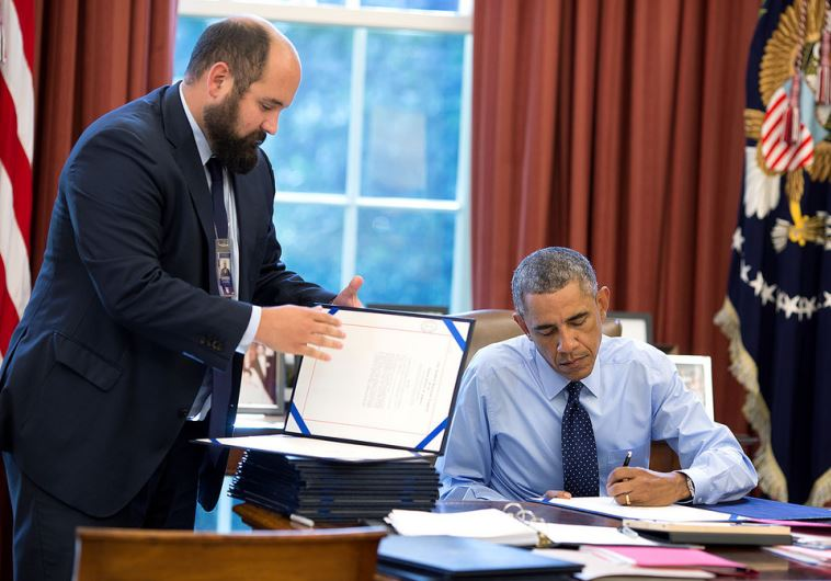 President Barack Obama, assisted by Deputy Staff Secretary Ted Chiodo, signs bills in Oval Office