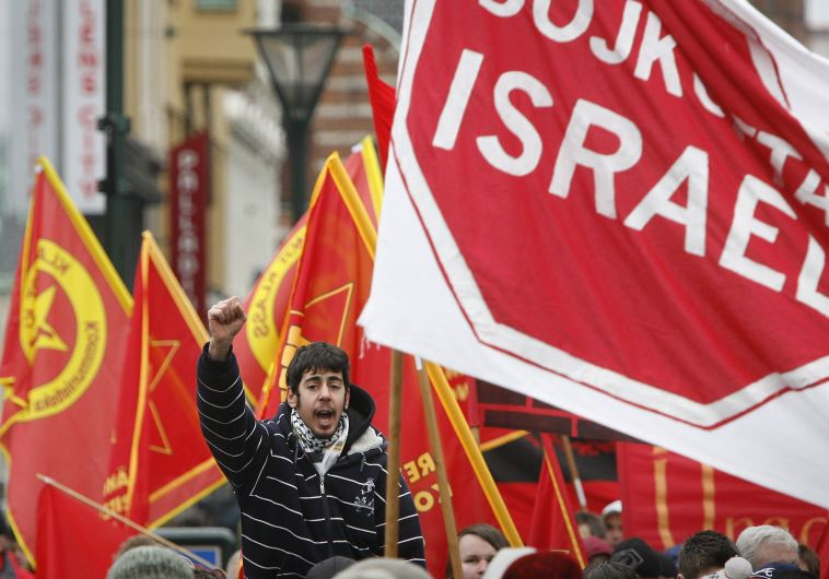 """A protester chants slogans near a banner reading """"Boycott Israel"""" during an anti-Israel march"""