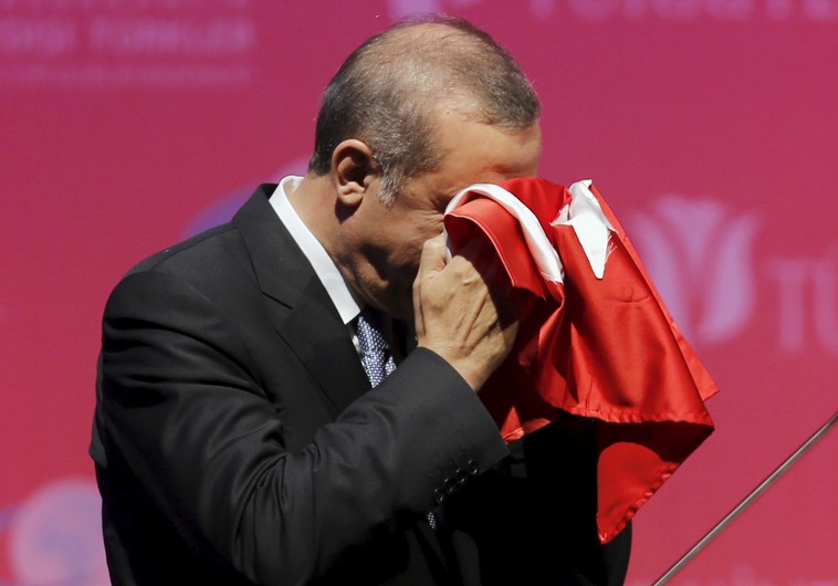 Turkey's President Recep Tayyip Erdogan kisses a handmade Turkish flag in Ankara