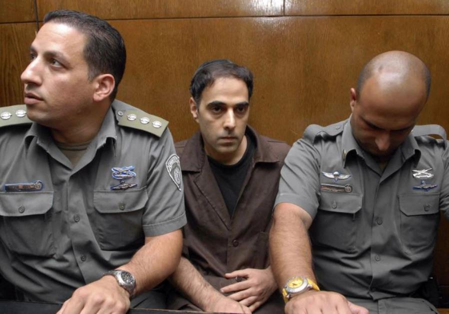 Israeli prison guards sit beside Yigal Amir (C), the assassin of Yitzhak Rabin