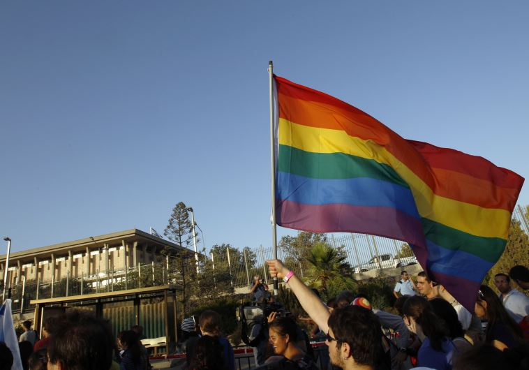An activist waves an LGBT flag near Israel's Knesset building