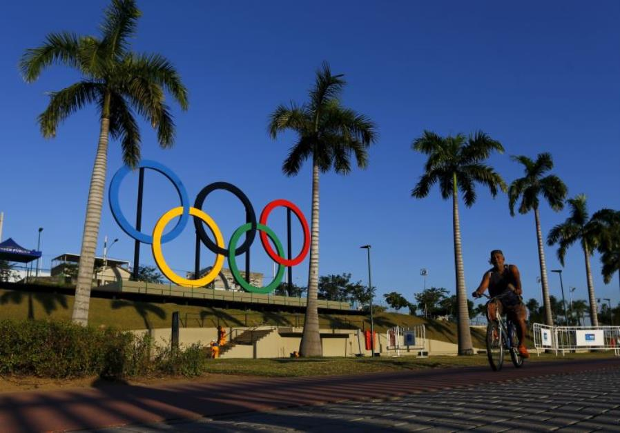 A man exercises next to the Olympic rings placed at the Madureira Park ahead the Rio 2016 Olympics