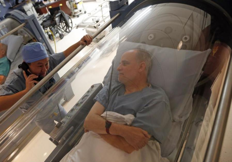 Doctor Andy Chiou (L) speaks to patient Carl Dolson in a hyperbaric chamber in Peoria, Illinois
