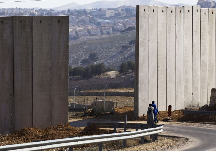 Palestinians walk near an opening in Israel's security fence east Jerusalem