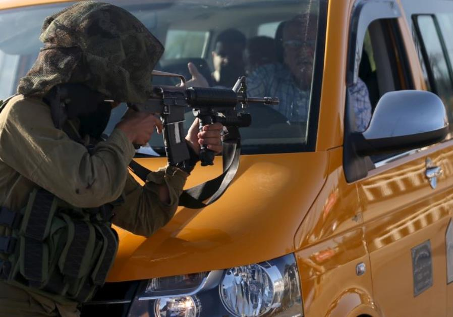 A driver stops his vehicle in front of an IDF soldier who is aiming his weapon at demonstrators