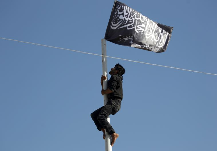 A member of al-Qaida's Nusra Front climbs a pole where a Nusra flag was raised in Ariha