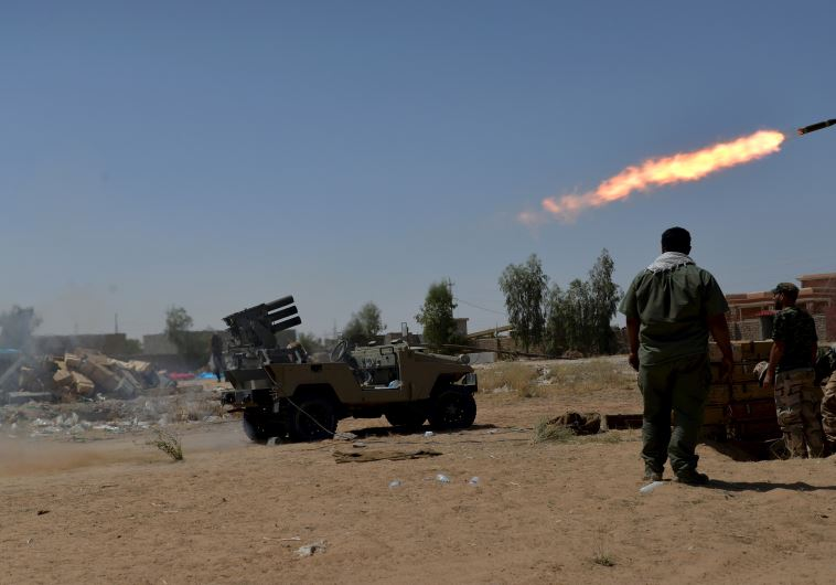 Shiite fighters launch a rocket towards Islamic State militants on the outskirt of Bayji