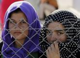 Yazidi refugees stand behind fences in the southern Turkish town of Midyat