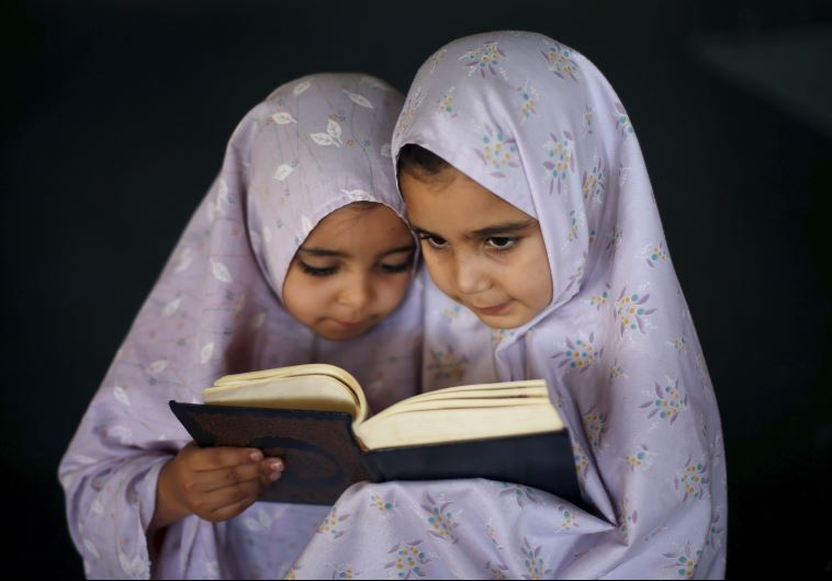Palestinian girls read the Koran as they attend a Koran memorization lesson during summer vacation