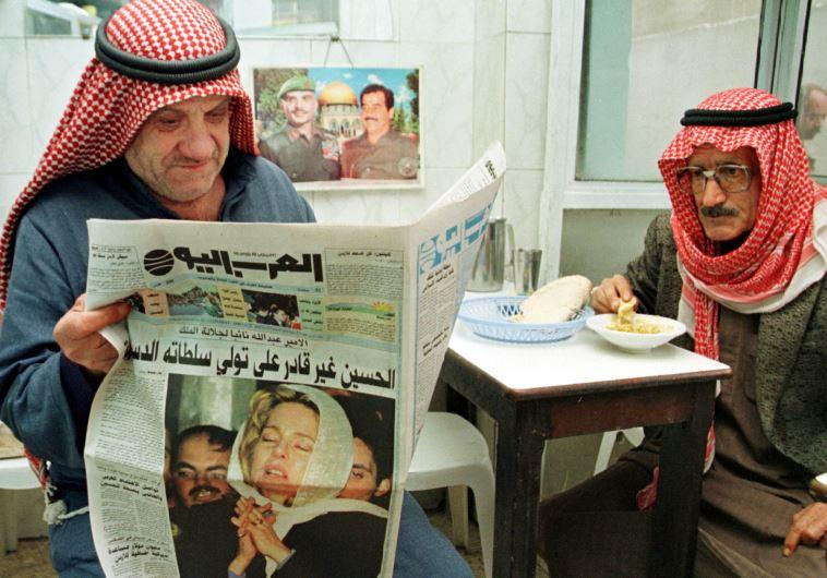 Jordanians read a newspaper in a popular Amman restaurant