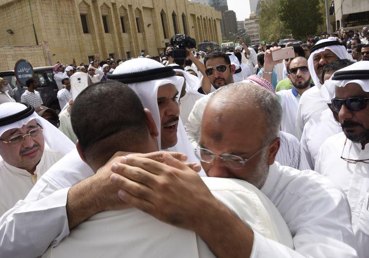 Kuwaiti Information Minister Sheikh Salman al-Humoud al-Sabah (C) consoles worshipers