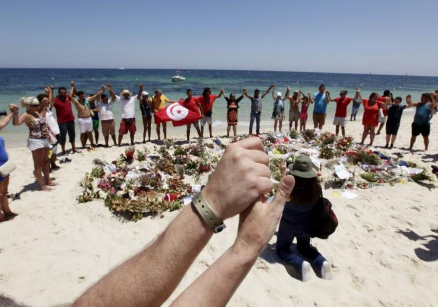 People join hands as they observe a minute's silence in memory of those killed in Tunisia