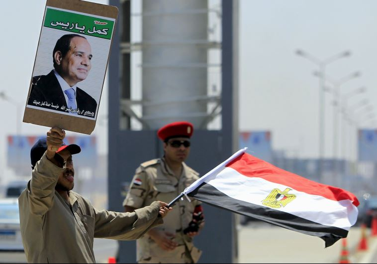 A man carrying a portrait of Egyptian President Abdel Fattah al-Sisi and an Egyptian flag