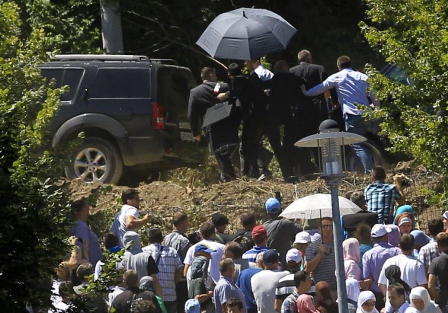 Bodyguards use umbrella to protect Serbia's Prime Minister Aleksandar Vucic