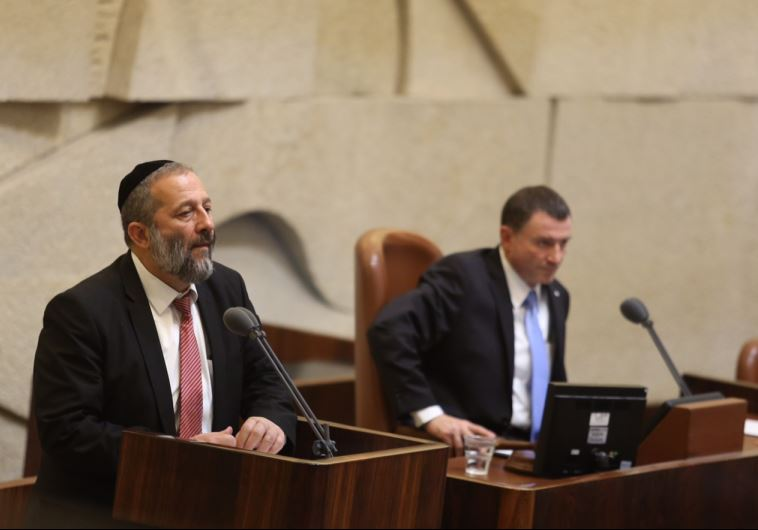 Economy Minister Aryeh Deri (L) speaks to the Knesset as speaker Yuli Edelstein looks on